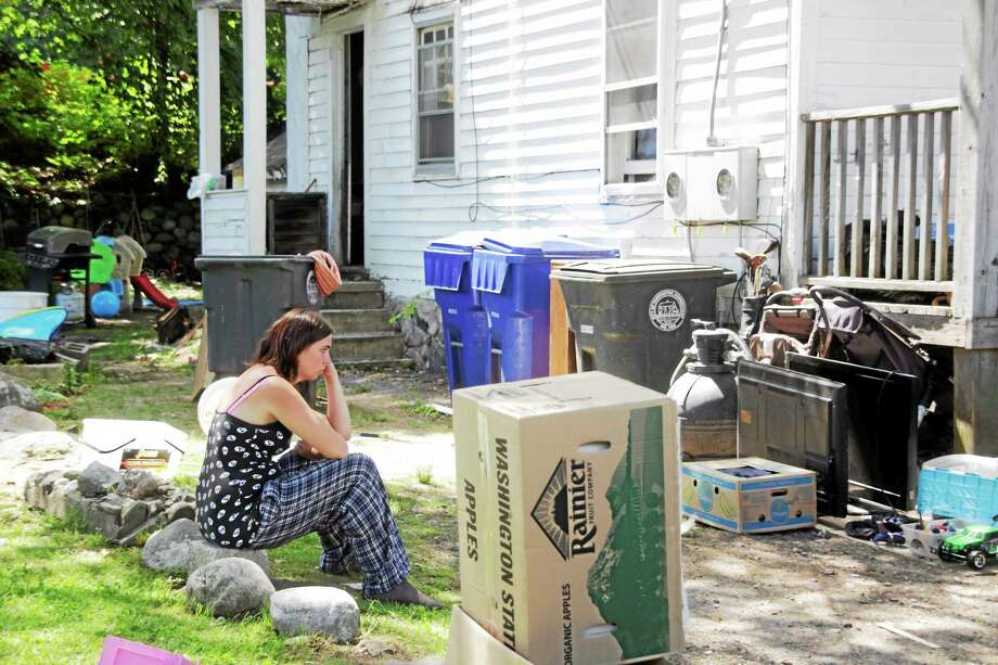A woman sits in front of a home at 30 South Chapel St. in Torrington, which was badly damaged and deemed unlivable following a two-alarm fire Friday evening. Photo: Shako Liu — The Register Citizen