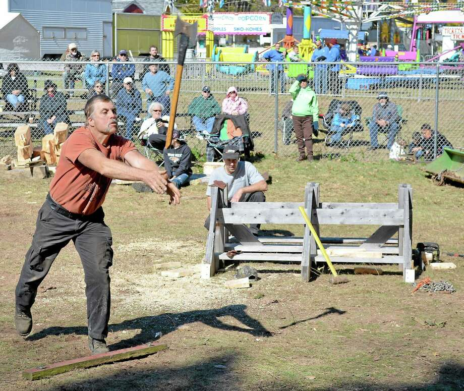 Harv Gereg, left of Warren, throws an ax in the final round to determine first place in the ax throwing competition as he and Tom Kass of Holyoke Mass., center, tied in the initial round of competition. The ax throwing and wood cutting competiton was part of the annual Riverton Fair on Saturday. Photo: Register Citizen File Photo