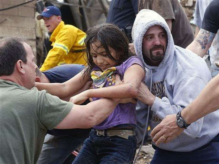 A child is passed along a human chain of people after being pulled from the rubble of the Plaza Towers Elementary School in Moore, Okla., and passed along a human chain of rescuers Monday, May 20, 2013. A tornado as much as half a mile (.8 kilometers) wide with winds up to 200 mph (320 kph) roared through the Oklahoma City suburbs Monday, flattening entire neighborhoods, setting buildings on fire and landing a direct blow on an elementary school. (AP Photo Sue Ogrocki) Photo: AP / 2013 AP