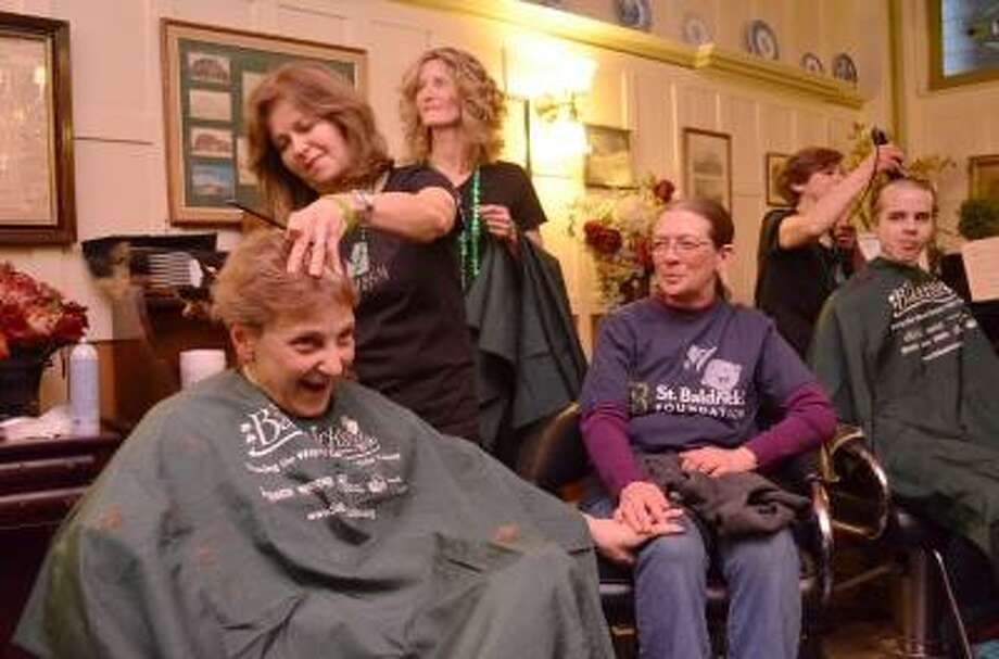 Vikki Borrelli held onto Cheri Mills, a five time veteran of the St. Baldrick's event, as she got her head shaved.