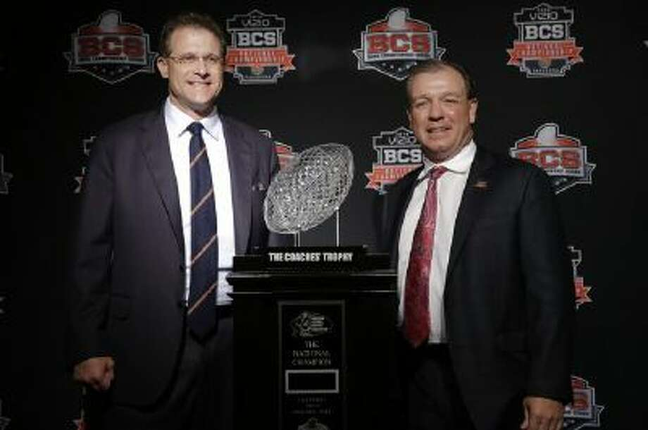 Auburn head coach Gus Malzahn, left, and Florida State head coach Jimbo Fisher pose with The Coaches' Trophy during a news conference for the NCAA BCS National Championship Game, which kicks off at 8:30 p.m. Monday.