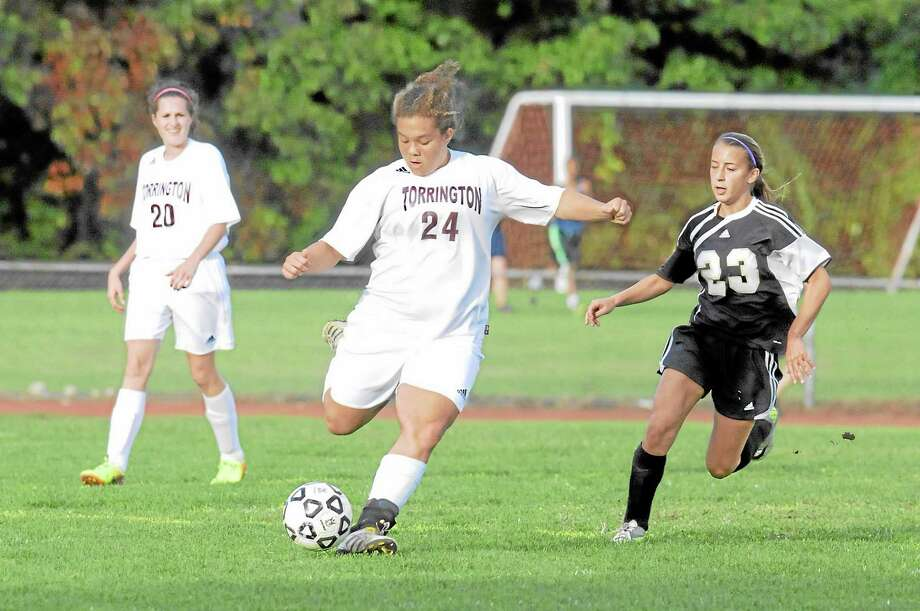 Torrington's Kendra Covington kicks the ball upfield as Woodland's  Jessica Rodrigues defends. Woodland won 3-2. Photo: Laurie Gaboardi — Register Citizen