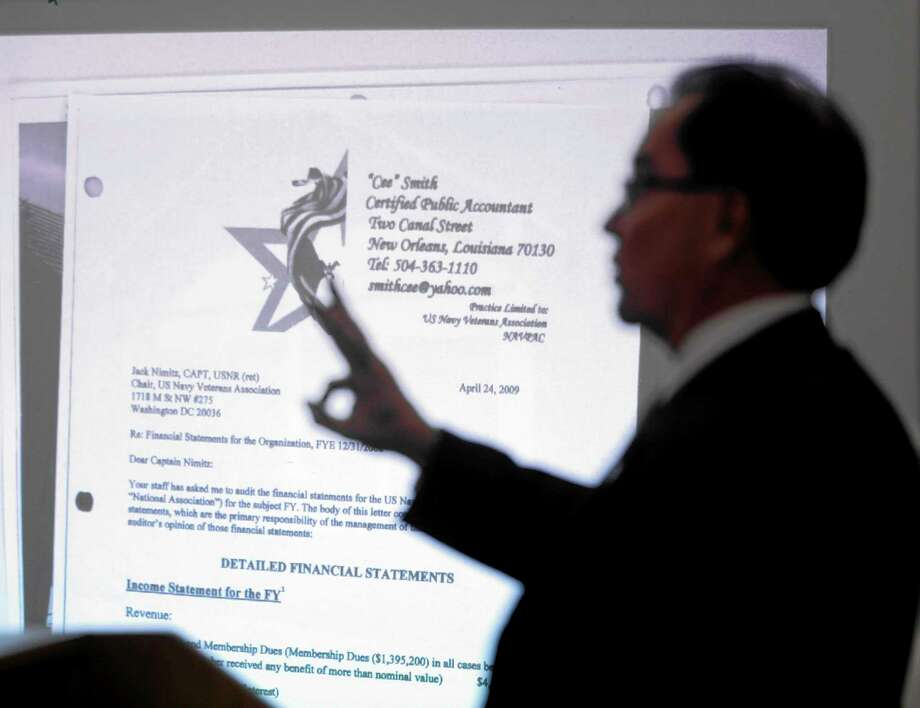 Assistant Ohio Attorney General Brad Tammaro displays evidence in the fraud trial of a man calling himself Bobby Thompson Monday, Oct. 7, 2013, in Clevelan. Thompson, 67, who authorities have identified as John Donald Cody, is charged with masterminding a $100 million multi-state fraud under the guise of helping Navy veterans. (AP Photo/Mark Duncan) Photo: AP / AP