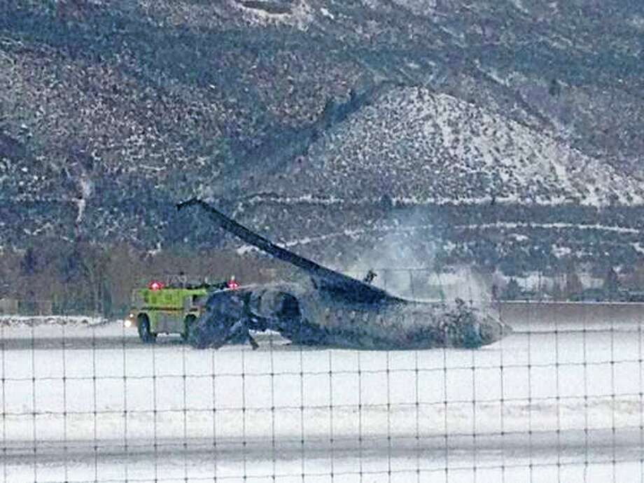 Emergency crews respond as a small plane lies on a runway at Aspen Airport in western Colorado after it crashed upon landing Sunday, Jan. 5, 2014. Emergency crews are responding to a fiery plane crash at Aspen Airport in western Colorado. (AP Photo/Corey Morris-Singer) Photo: AP / AP
