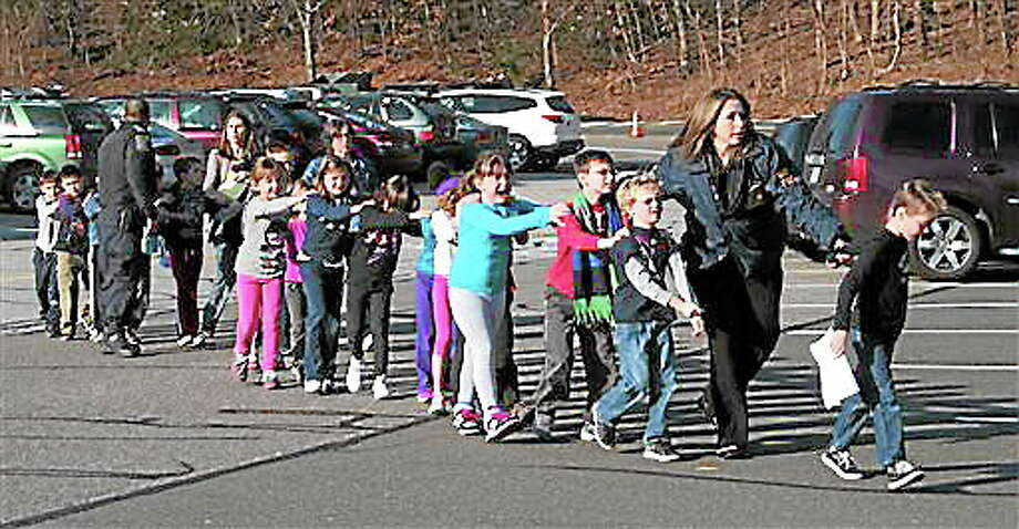 FILE - In this photo provided by the Newtown Bee, Connecticut State Police lead a line of children from the Sandy Hook Elementary School in Newtown, Conn. on Friday, Dec. 14, 2012 after a shooting at the school.  Hundreds of children at the school that day survived, but the horrors have been especially difficult to overcome for some of the 6- and 7-year-olds who witnessed the bloodbath, even as the school year resumed in autumn of 2013. (AP Photo/Newtown Bee, Shannon Hicks, File) MANDATORY CREDIT: NEWTOWN BEE, SHANNON HICKS Photo: AP / Newtown Bee