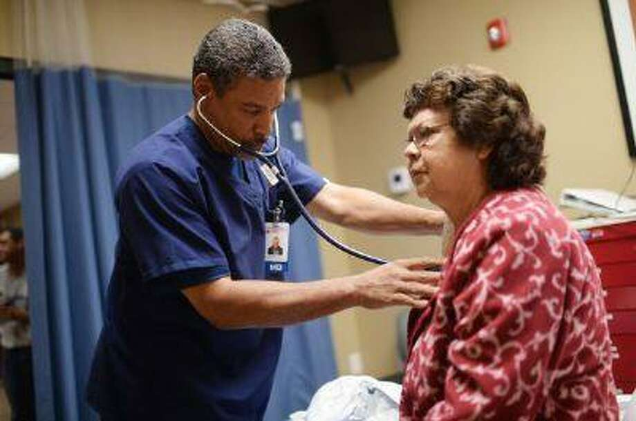 Dr. Ron Price examines Olga Thein at a First Choice emergency room in Colorado Springs last week. Photo: DP / Copyright - 2013 The Denver Post, MediaNews Group.