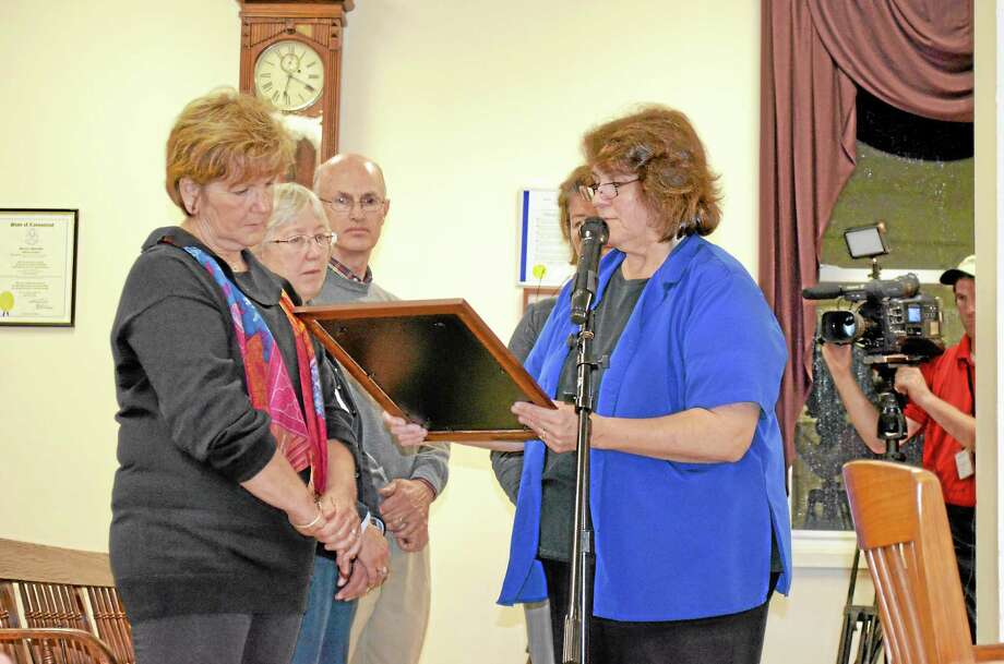 Winchester Mayor Maryann Welcome presents a plaque to the family of former Mayor John Groppo. Photo: Mercy Quaye — Register Citizen