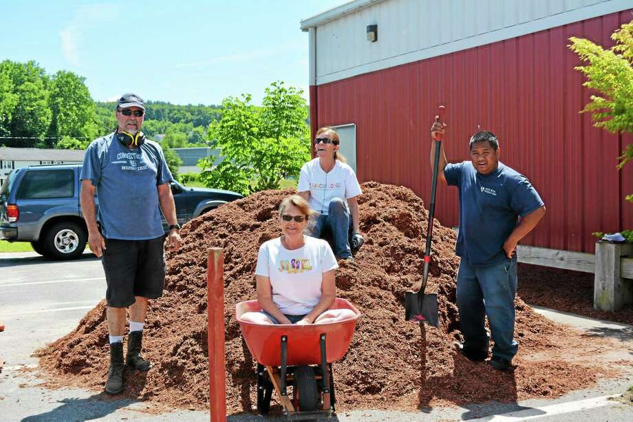The Alcoa-Howmet Day of Caring volunteers taking a break from laying mulch Friday. On the left is Dave Monschein, on the mulch pile is Julie Ziemann, on the right is Kham Thongchampasy, and in the wheelbarrow is Cathy Daly. Daly's been volunteering for the United Way Day of Caring event for 28 years. Photo: Jenny Golfin — The Register Citizen