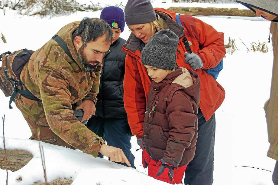Noah Cinel and his mother, Justine, huddle around tour guide Andrew Dobos as he points to animal tracks in the snow. Dobos and his wife, Deneen Bernier, searched out wildlife with a pack of adults and children Sunday at White Memorial Conservation Center. Photo: Isaac Avilucea—Register Citizen