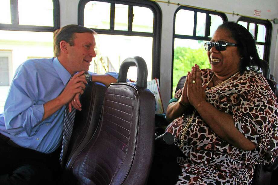 U.S. Sen. Chris Murphy talks to Mary Ann Singletary, 57, of Torrington, during a bus ride in the city Friday. The ride is part of the senator's efforts to stay connected and talk to his constituents. Photo: Esteban L. Hernandez — The Register Citizen
