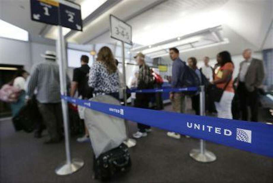 In this photo taken May 8, 2013, groups of passengers wait at a United Airlines gate to board a flight at O'Hare International Airport in Chicago. (AP Photo/M. Spencer Green) Photo: AP / AP