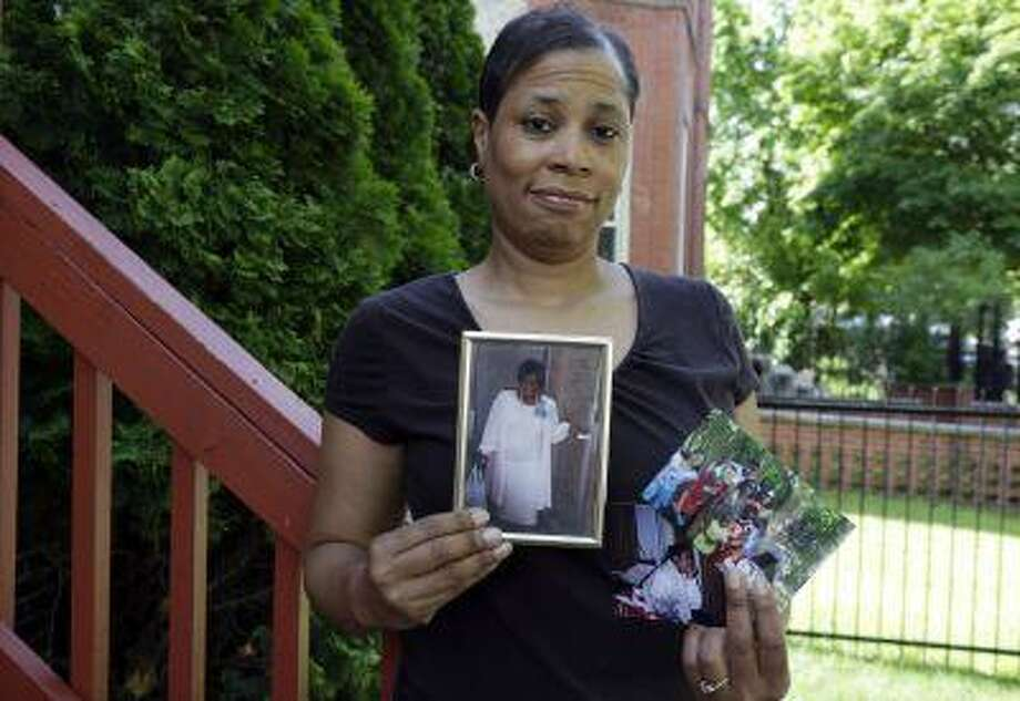 In this May 31, 2013 photo, breast cancer survivor Alicia Cook holds photos of family members who have also been afflicted by breast cancer, outside her home in Chicago. (AP Photo/M. Spencer Green) Photo: ASSOCIATED PRESS / AP2013