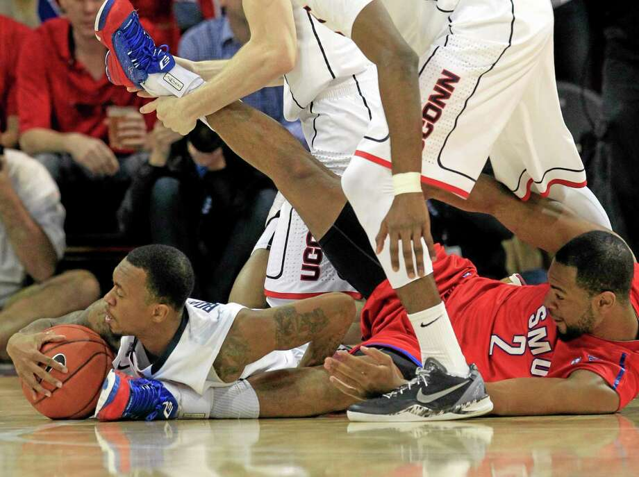 UConn guard Ryan Boatright, left, grabs a loose ball as SMU forward Shawn Williams joins him on the floor during the first half of the Mustangs' 74-65 win over the 17th-ranked Huskies on Saturday in Dallas. Photo: John F. Rhodes — The Associated Press  / FR170608 AP