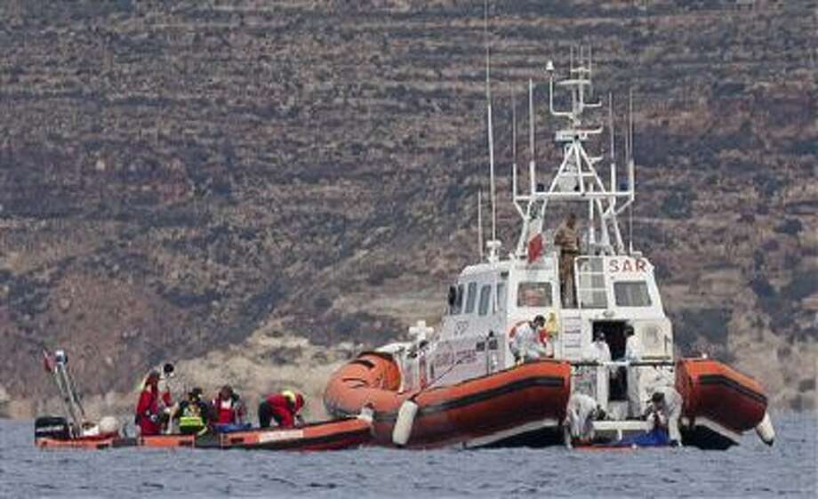 Italian Coast Guard personnel recover a body bag on their patrol boat in Lampedusa island, Italy, Tuesday, Oct. 8, 2013. Photo: AP / AP