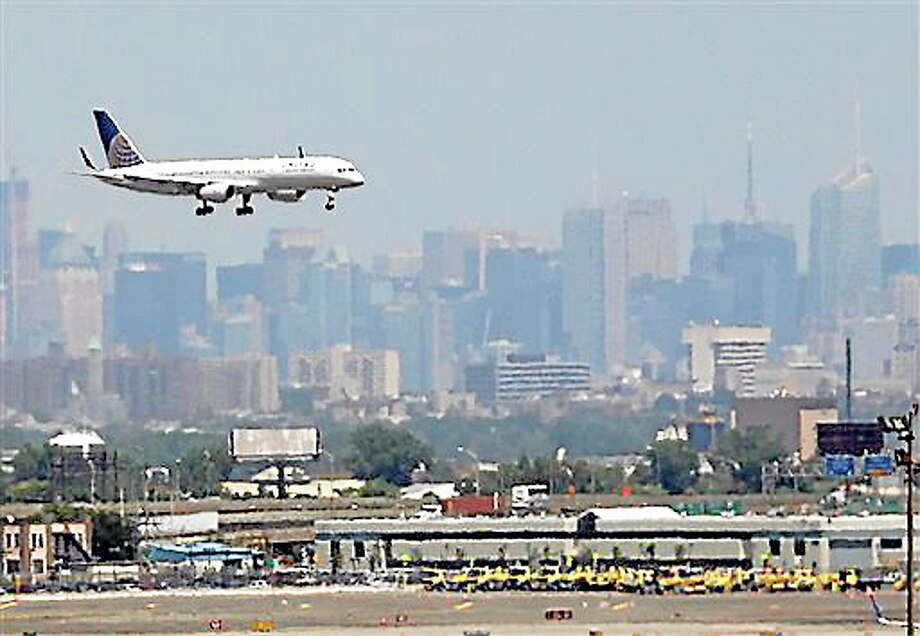 FILE - In this July 10, 2012 file photo, a United plane prepares to land at Newark Liberty International Airport in Newark, N.J., with the New York City skyline in the background. Commercial airline flights moved smoothly throughout most of the country on Sunday, April 21, 2013, the first day air traffic controllers were subject to furloughs resulting from government spending cuts, though some delays appeared in the late evening in and around New York. The real test, however, will come Monday, when traffic ramps up. (AP Photo/Julio Cortez, File) Photo: AP / AP