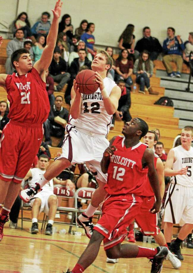 Torrington's Mitch Zagrodnik drives between Wolcott's Cole Phelps (20) and Shamari Thomas (12) on his way to the basket. Zagrodnik finished with 12 points in Torrington's 61-44 win over Wolcott. Photo: Marianne Killackey — Special To The Register Citizen  / 2013