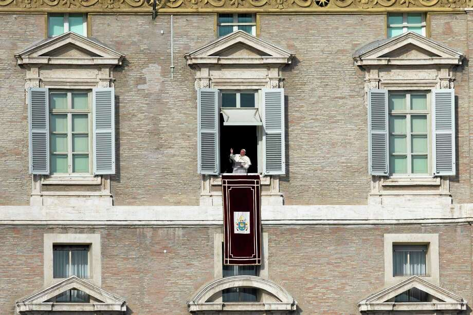 """Pope Francis delivers his blessing during the Angelus noon prayer he celebrated from the window of his studio overlooking St. Peter's Square at the Vatican, Wednesday, Jan. 1, 2014. """"We are all children of one heavenly father, we belong to the same human family and we share a common destiny,"""" Francis said, as tens of thousands of faithful, tourists and Romans jammed St. Peter's Square. (AP Photo/Andrew Medichini) Photo: AP / AP"""