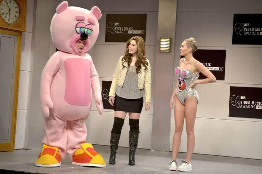 """This Oct. 5, 2013 photo released by NBC shows, from left, Bobby Moynihan, Vanessa Bayer and guest host Miley Cyrus in a scene from the late-night comedy series """"Saturday Night Live,"""" in New York. Photo: AP / Episodic"""