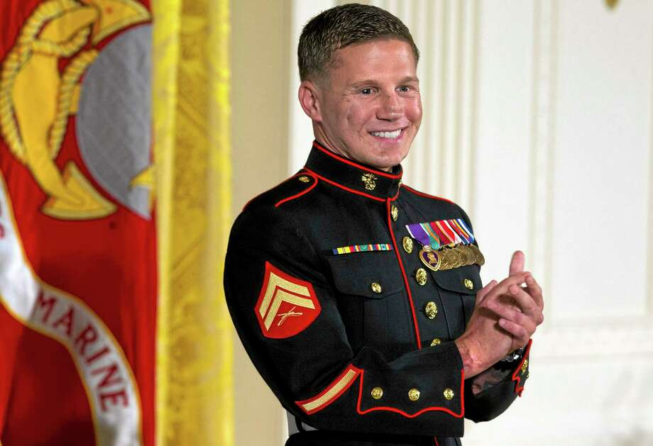 "Retired Marine Cpl. William ""Kyle"" Carpenter applauds his medical team as they stand to be acknowledged by President Barack Obama during a ceremony presenting Carpenter with the Medal of Honor for conspicuous gallantry, Thursday, June 19, 2014, in the East Room of the White House in Washington. Carpenter received the Medal of Honor for his courageous actions while serving as an Automatic Rifleman in Helmand Province, Afghanistan. (AP Photo/Jacquelyn Martin) Photo: AP / AP"