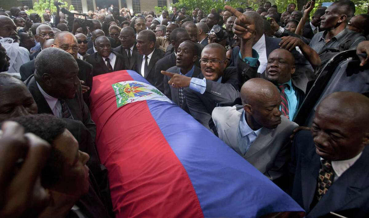 """Friends and family of Haiti's late Dictator Jean-Claude """"Baby Doc"""" Duvalier carry his flag draped coffin back to the funeral home after his funeral ceremony in Port-au-Prince, Haiti, Saturday, Oct. 11, 2014. Many had wondered whether the self-proclaimed """"president for life"""" would receive a state funeral following his death last Saturday from a heart attack at age 63, but Duvalier's attorney announced late this week that friends and family would arrange a simple and private funeral. (AP Photo/Dieu Nalio Chery)"""
