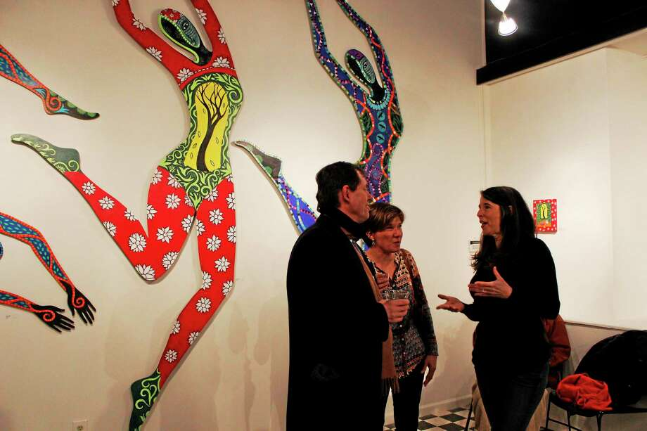 """Danielle Mailer, right, tells visitors about some of the art involved in her """"body Language, 2013"""" display, which opened at Five Points Gallery on Friday. Photo: Shako Liu—Register Citizen"""