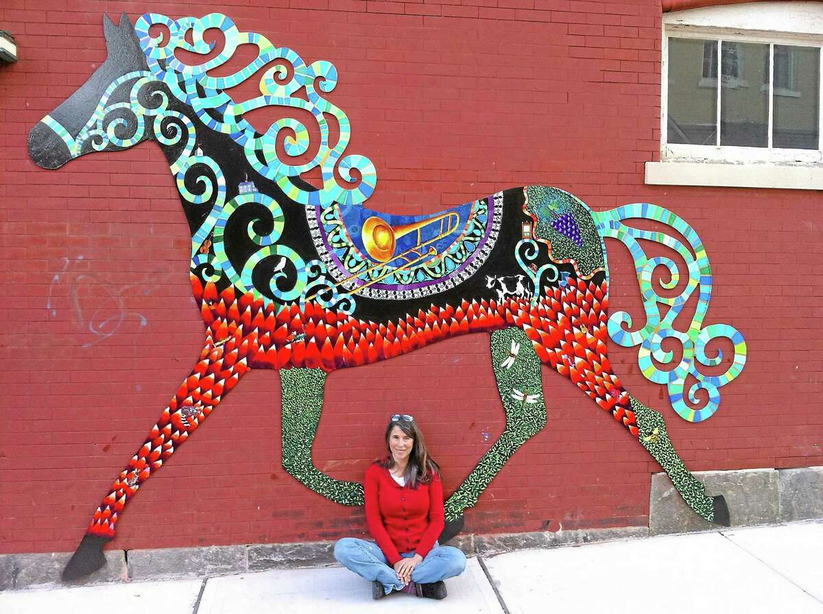 Danielle Mailer pictured with her horse artwork in downtown Torrington.