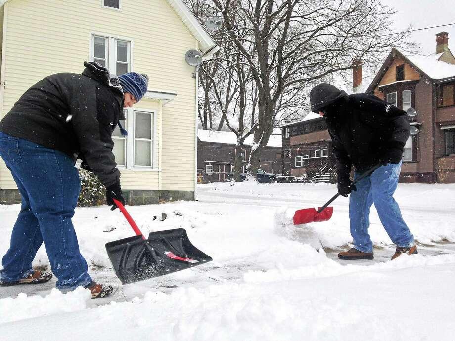 Mercy Quaye-Register Citizen Amber and Eric Pelletier shovel the sidewalk outside of their home on Wetmore Avenue in Winsted Thursday. Photo: Journal Register Co.