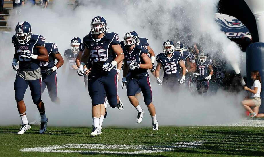UConn players run onto the field before the Huskies' 36-10 loss to Temple on Sept. 27 in East Hartford. Photo: Michael Dwyer — The Associated Press  / AP
