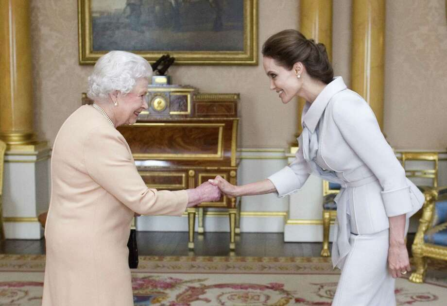 U.S actress Angelina Jolie, right, is presented with the Insignia of an Honorary Dame Grand Cross of the Most Distinguished Order of St Michael and St George by Britain's Queen Elizabeth II at Buckingham Palace, London, Friday, Oct. 10, 2014.  Jolie received an honorary damehood (DCMG) for services to UK foreign policy and the campaign to end war zone sexual violence. (AP Photo/Anthony Devlin, pool) Photo: AP / PA pool