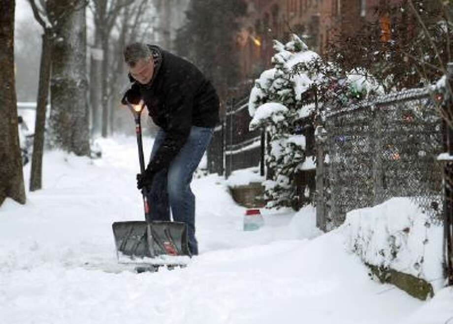 New York City Mayor Bill de Blasio shovels the sidewalk in front of his house in New York, Friday, Jan. 3, 2014.