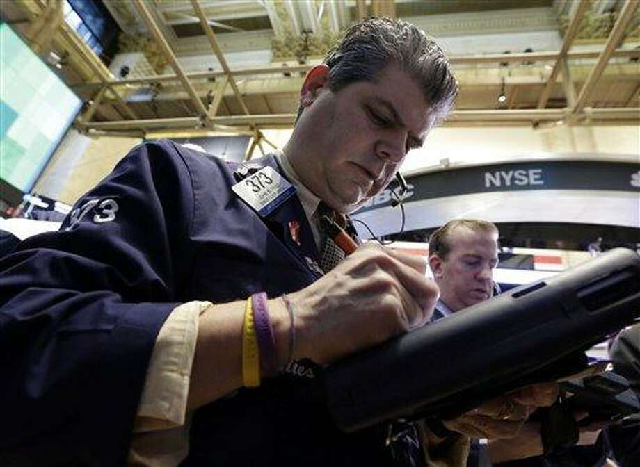 Trader John Panin, left, works on the floor of the New York Stock Exchange Wednesday, March 13, 2013. Investors are calling an end to the past week's remarkable rally, with many cashing in on stocks Wednesday despite more strong economic data out of the U.S. (AP Photo/Richard Drew) Photo: ASSOCIATED PRESS / AP2013