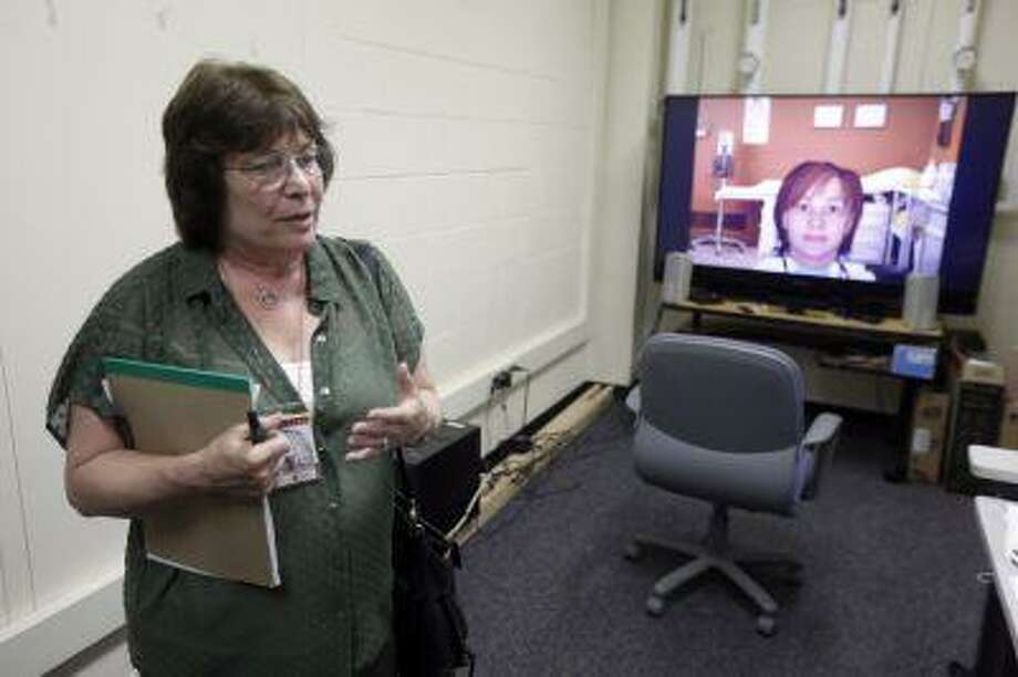 In this Thursday, July 18, 2013 photo, Nadine Martin, a communication sciences professor speaks in view of an avatar on a television screen during an interview with the Associated Press at Temple University in Philadelphia. Martin and other researchers are working to develop a virtual speech therapist to help those trying to overcoming the language disorder known as aphasia. (AP Photo/Matt Rourke) Photo: AP / AP