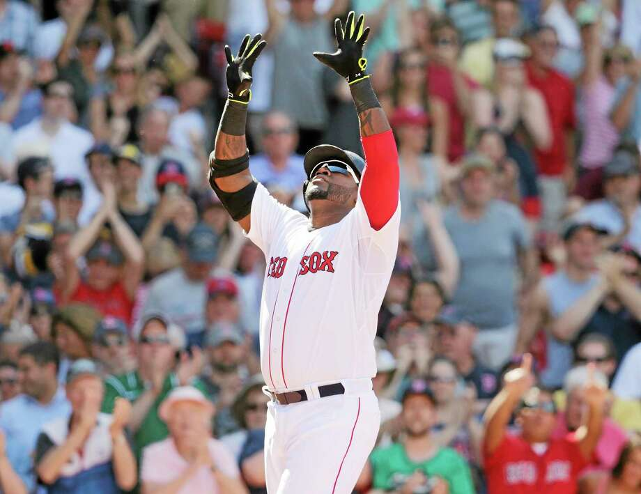 Red Sox designated hitter David Ortiz raises his arms as he crosses home plate after his game-tying, solo home run during the 10th inning of Wednesday's game at Fenway Park in Boston. Photo: Charles Krupa — The Associated Press  / AP