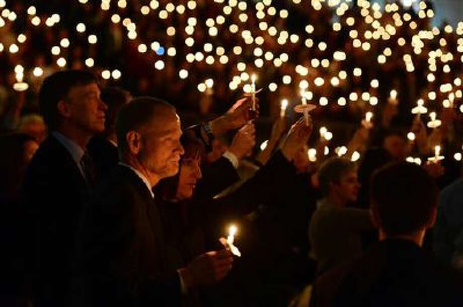 Michael and Desiree Davis, parents of Claire Davis, hold up candles with others at a memorial service held for their daughter Wednesday in Denver. Behind them at left is Colorado Gov. John Hickenlooper. Claire Davis, 17, was fatally shot at her suburban Denver high school on Dec. 13 by a fellow student, who then killed himself. Photo: AP / The Denver Post