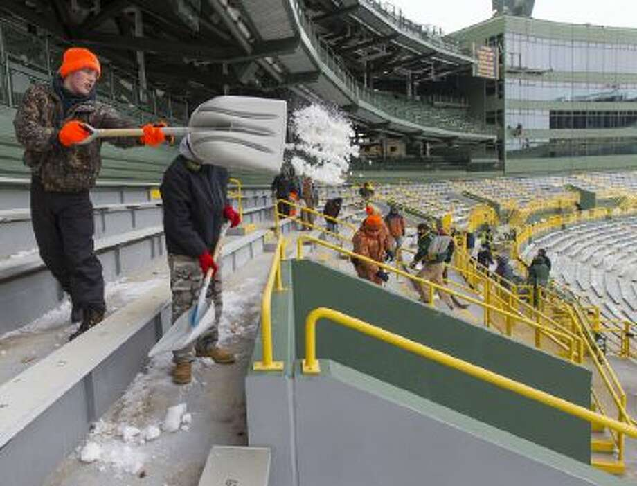 Workers clear ice and snow from the seats at Lambeau Field on Friday, Jan. 3, 2014, in Green Bay, Wis.
