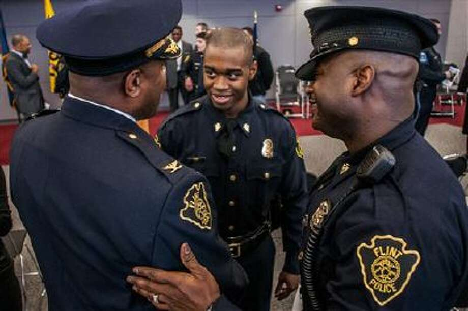 A new officer is congratulated in Flint, Mich. Some cities, like Salt Lake City, are looking to give their police officers more training. Photo: AP / Flint Journal