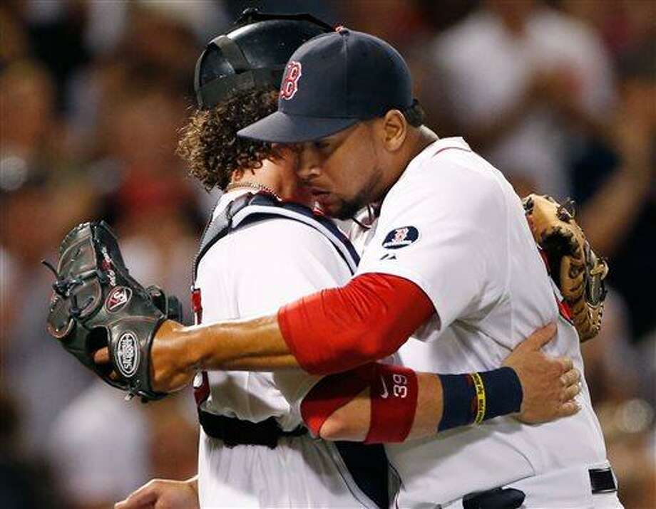 Boston Red Sox closer Pedro Beato, right, hugs catcher Jarrod Saltalamacchia as they celebrate the Red Sox's 8-2 victory over the Seattle Mariners in a baseball game at Fenway Park in Boston on Tuesday, July 30, 2013. (AP Photo/Elise Amendola) Photo: AP / AP
