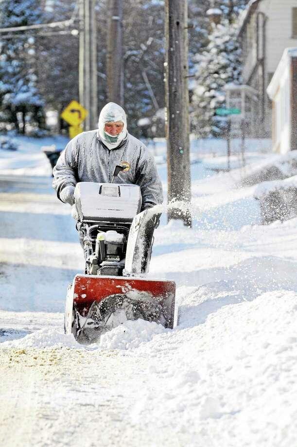 Rich Howard cleans a sidewalk in Torrington in frigid temperatures on Jan. 3 following Thursday night's snowstorm. Photo: Laurie Gaboardi—Register Citizen