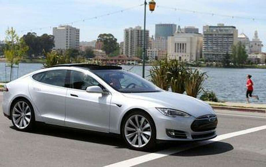 San Jose Mercury News reporter Dana Hull drives a Tesla Model S sedan past Lake Merritt in Oakland, Calif., on Thursday, April 11, 2013. Tesla Motors loaned the car to Hull for a few days to test-drive. Photo: JANE TYSKA / THE OAKLAND TRIBUNE/BAY AREA NEWS GROUP