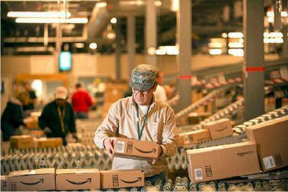 "In this Monday, Dec., 1, 2008, file photo, an <a href=""http://Amazon.com"">Amazon.com</a> employee grabs boxes off the conveyor belt to load in a truck at their Fernley, Nev., warehouse. <a href=""http://Amazon.com"">Amazon.com</a> Inc. says it is adding 7,000 jobs in 13 states, beefing up staff at the warehouses where it fills orders, and in its customer service division. The company says it will add 5,000 full-time jobs at its U.S. distribution centers, which currently employ about 20,000 workers who pack and ship customer orders. (AP Photo/Scott Sady, File)"