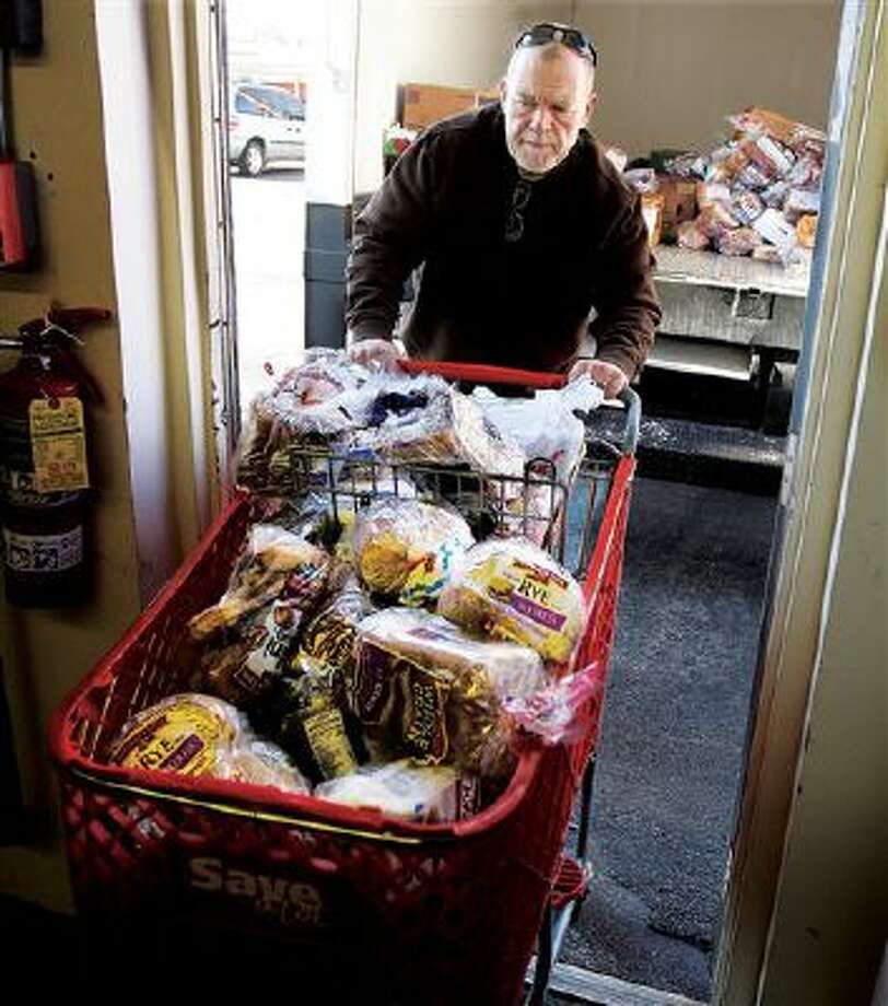 Volunteer Greg Harris pushes a basket of bread into the Guardian Angel Pantry at Catholic Charities in Alton, Ill. Federal benefit cuts to programs like SNAP, the Supplemental Nutrition Assistance Program, have left area food pantries with more people in need. Photo: AP / The Telegraph