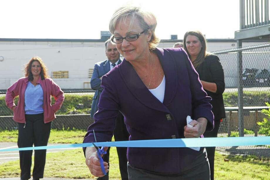 Torrington Mayor Elinor Carbone cuts a ribbon to commemorate a new city parking lot on Franklin Street on Thursday in Torrington. Photo: Esteban L. Hernandez — Register Citizen