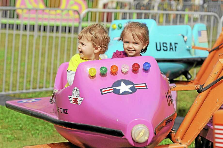 A.J. Pratt,1, and his 2-year-old sister, Emma, of Middlebury, enjoy one of the many rides available at the 157th annual Harwinton Fair. Photo: Laurie Gaboardi—Register Citizen