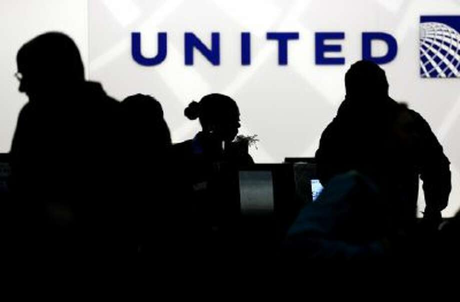 Holiday travelers check in at the United Airlines ticket counter at Terminal 1 in O'Hare International Airport in Chicago on Saturday, Dec. 21, 2013.