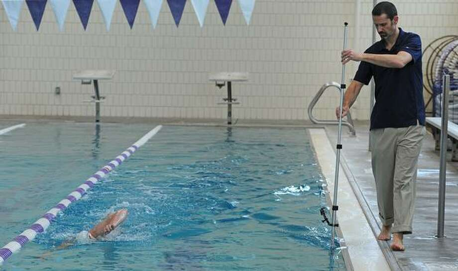 DENVER, CO- MARCH 6:   Veronica Penney, who is a senior at CU-Boulder and  a member of Triathlon Team is videotaped by her coach Dave Sheanin. Sheanin uses a GoPro video camera to be able to look more closely at the stroke of the athlete and make changes.  The two are training at the North Boulder Recreation Center pool in Boulder, CO on March 7th, 2013.(Photo By Helen H. Richardson/ The Denver Post) Photo: DP / Copyright - 2013 The Denver Post, MediaNews Group.