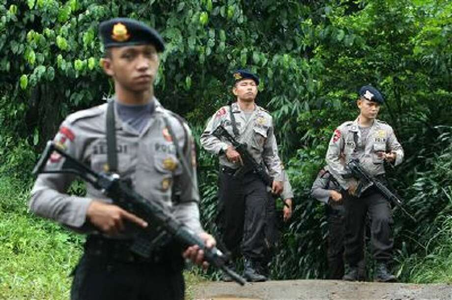 Police officers patrol the area near a house Wednesday that was used as a hideout by suspected militants following an overnight raid in Ciputat, Indonesia. Indonesia's elite anti-terrorism squad shot and killed six suspected militants amid New Year's Eve celebrations. Photo: AP / AP