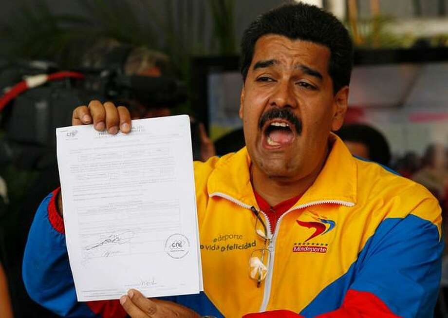 Venezuela's acting President Nicolas Maduro shows his certificate after registering his presidential candidacy to replace late President Hugo Chavez at the national electoral council in Caracas, Venezuela, Monday, March 11, 2013. Presidential elections were announced to take place on April 14, after the death of Chavez on March 5. (AP Photo/Ariana Cubillos) Photo: ASSOCIATED PRESS / AP2013