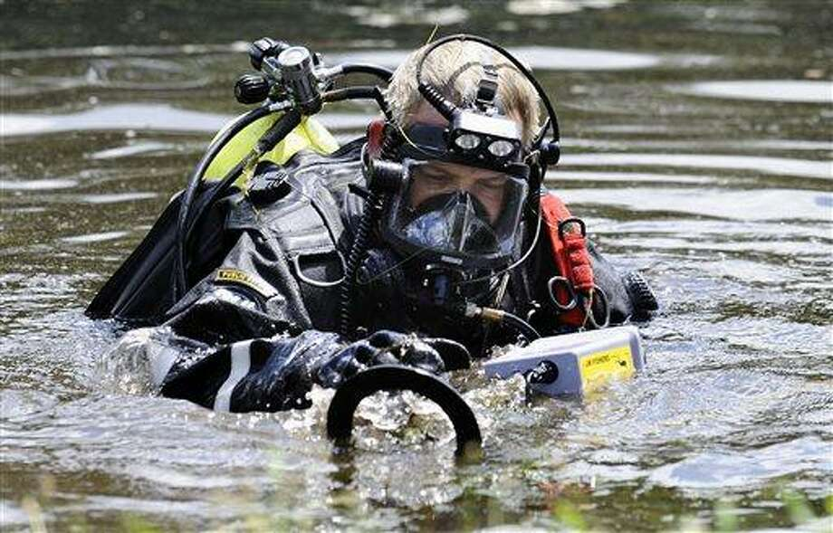 A Connecticut State Police dive team member searches Pine Lake in Bristol, Conn., the hometown of the former New England Patriots player Aaron Hernandez,  Monday, July 29, 2013. Police divers were in Pine Lake on Monday and other officers could be seen combing the water's edge. Hernandez has pleaded not guilty to murder in the death of Odin Lloyd, a 27-year-old Boston semi-professional football player. (AP Photo/Jessica Hill) Photo: AP / FR125654 AP