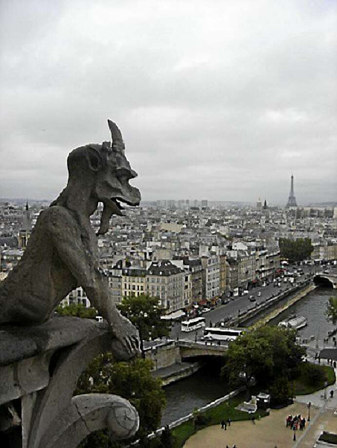 A gargoyle looks out over Paris from Notre Dame. The Eiffel Tower can be seen in the background (at upper right). Photo: Photo By Christine Tansey