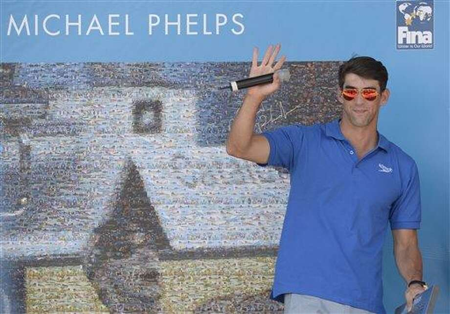 Former Olympic and world swimming champion Michael Phelps of the US attends the unveiling of a mosaic installed in his honour at the FINA Swimming World Championships in Barcelona, Spain, Sunday, July 28, 2013 .(AP Photo/Manu Fernandez) Photo: AP / AP